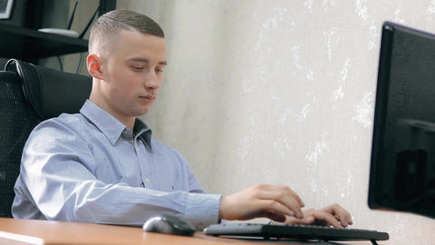 A young guy is working concentrated at the computer in the office Footage