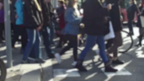 Blurred pedestrians walking toward the right in a crosswalk Footage