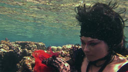 Young underwater model free diver in red dress photographs on camera in Red Sea Footage