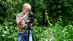 Young boy with video camera make movies about nature of green park background Footage