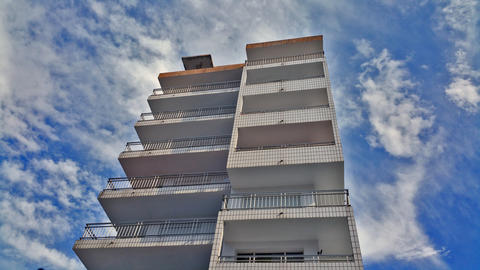 view from the bottom to the top of a multi-storey building against a blue sky フォト