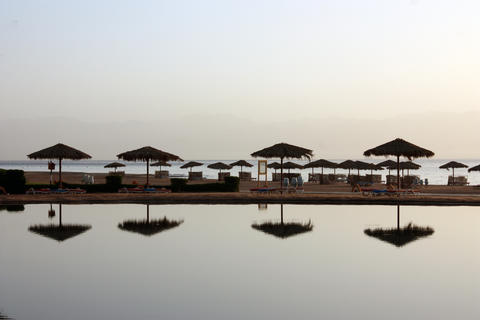 reflection of beach umbrellas from the sun in the water in the morning haze Fotografía