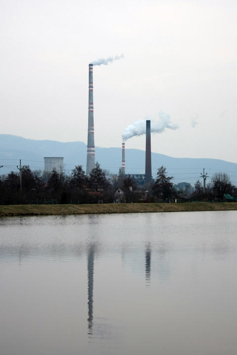view of the chimneys with white smoke, reflected in the water フォト