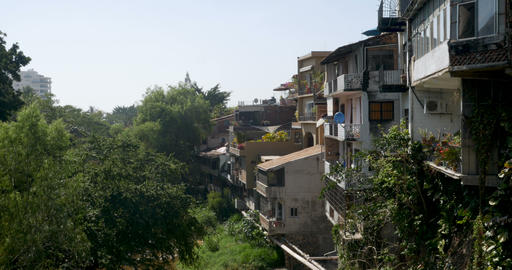 Houses built on a hillside overlooking lush trees and a river Image