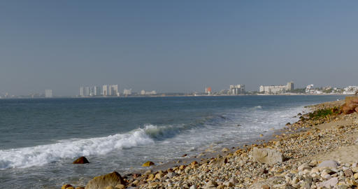 Waves crashing ashore a rocky beach with the hotels and high rises in the Footage