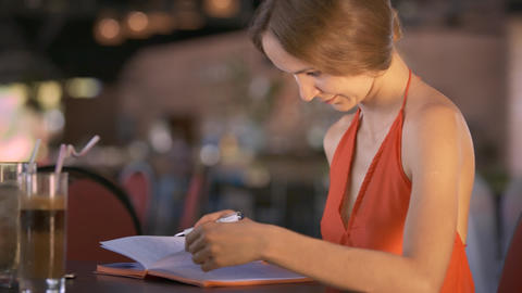 Girl Reads Diary Sitting at Table near Beverages Live Action