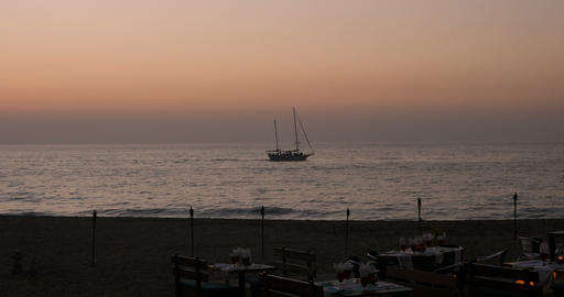 Boat sailing close to shore during sunset near a restaurant with romantic mood Image