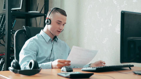 The young sociable guy the operator of the call center talking to people Footage