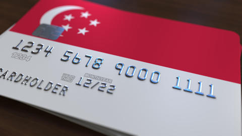 Plastic bank card featuring flag of Singapore. Singaporean banking system Live Action