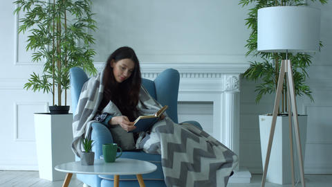 Pretty woman reading a book in armchair at home ビデオ