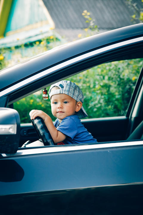 Little boy driving a car looking out the window フォト
