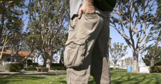 Low angle of a man with his hands in his back pockets of his cargo pants outside Footage