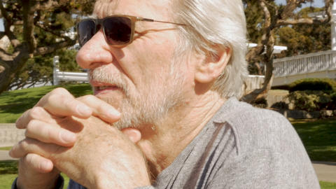 Attractive senior old man resting his head with his hands folded on his chin in Footage
