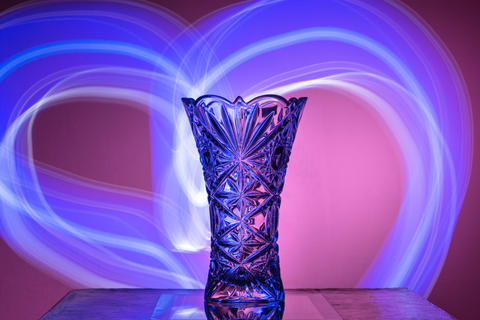 The crystal vase on a red background is illuminated by rays フォト
