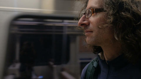 Handsome man with long hair standing on a subway platform as the metro train Footage