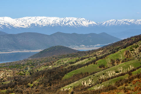Landscape of a lake between spring hills and snow-covered mountain peaks Fotografía