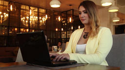Beautiful business woman typing text on a mobile computer sitting at a table in Footage