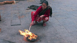 Woman near the holy fire on streets of Kathmandu in Nepal Footage