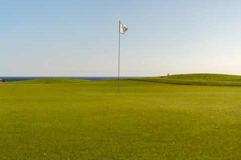 Green golf with flag and hole facing Atlantico フォト