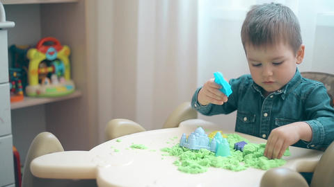 A little boy builds castles and various figures of green kinetic sand Footage