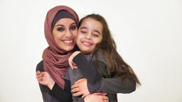 Young beautiful mother in hijab hugging her daughter and looking at camera Footage