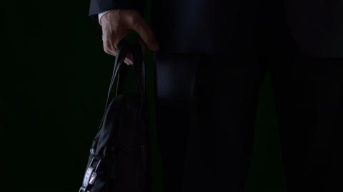 Businessman holding briefcase or business bag in hand. Low key dark background Footage