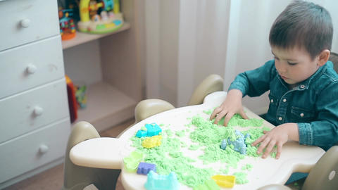 A small child is playing with kinetic sand and develops motor skills of hands Footage