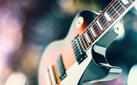 Close up shot of a guitar, over blured lights background Fotografía