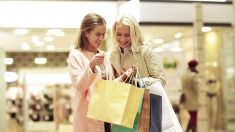 happy young women with shopping bags in mall Footage