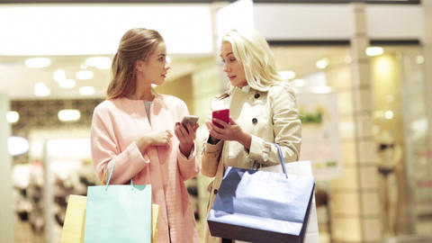 happy women with smartphones and shopping bags Footage