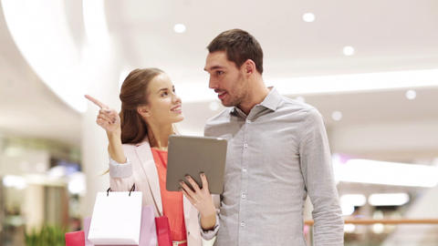 couple with tablet pc and shopping bags in mall Footage