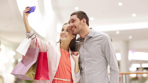 happy couple with smartphone taking selfie in mall Footage