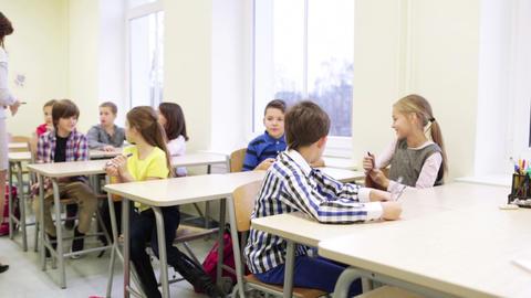 teacher giving pens to school kids in classroom Footage