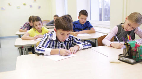 group of school kids writing test in classroom Footage