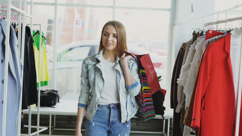 Dolly shot of attractive young lady walking slowly through modern shop. She is Footage