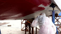 Worker paints metal of lower part of ship red color at shipyard in port Footage