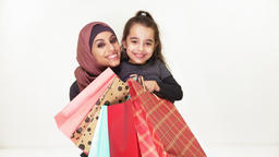 Young beautiful mother in hijab hugs her little daughter, holding shopping bags Footage