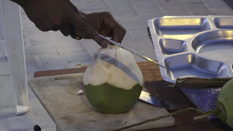 Man cleans a coconut with a knife. Maldives video Archivo