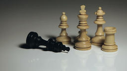 Chess Pieces: Black King Falls in front of White Bishop, Rook, Pawn, and King Live Action