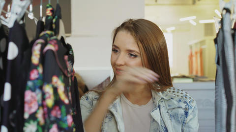 Young girl with long brown hair is looking through clothes on rails in modern Footage