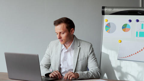 Portrait of a European male sitting at a laptop in the office with a white shirt Live Action
