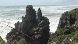 Waves on a rocky coast and mountains New Zealand Footage