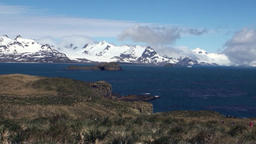 Snowy mountains on background of blue sky with clouds and ocean in Antarctica Footage