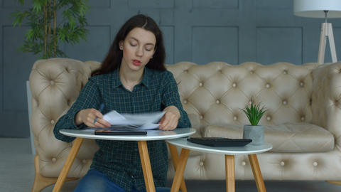 Frustrated woman with expense receipts at home Image