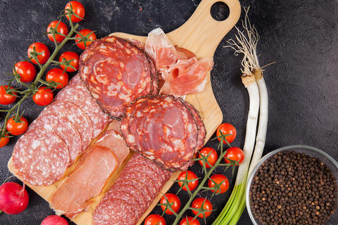 Meat appetizers next to tomatoes, radish and green onion Fotografía