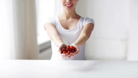close up of young woman showing cherry tomatoes Footage