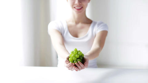 close up of young woman showing green grape bunch Footage