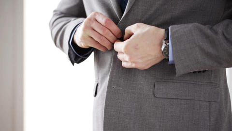 close up of man in suit fastening button on jacket Live Action