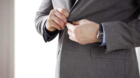 close up of man in suit fastening button on jacket Footage