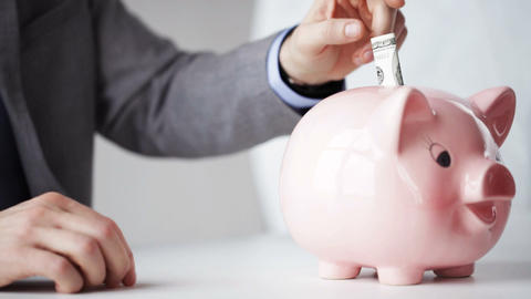 close up of man putting money into piggy bank Footage